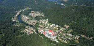 Obec Loučovice v pozadí s hrází přehrady Lipno.